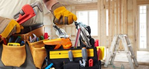 Builder handyman with construction tools. House renovation backg
